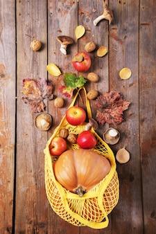 Outono plana leiga com mão feminina segurando o saco de corda turquesa com abóboras laranja.