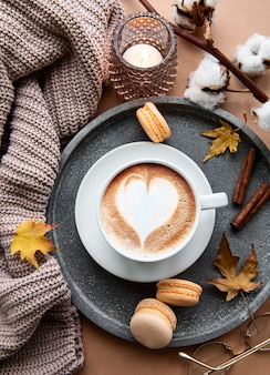 Outono plano deitado com uma xícara de café, cobertor quente, abóboras listradas decorativas, velas e folhas de outono