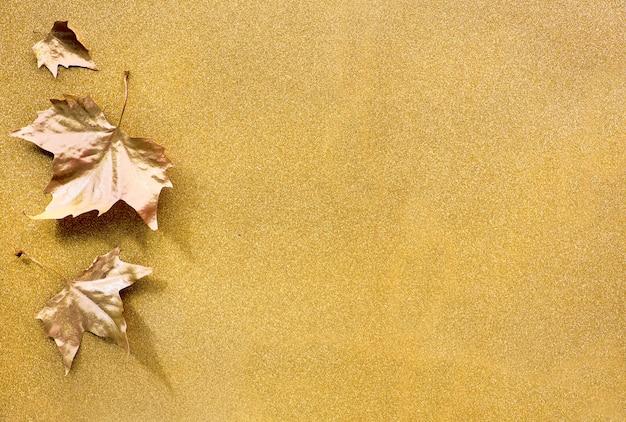 Outono plano leigos com folhas douradas pintadas e cópia espaço em papel dourado brilhante