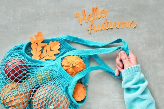 Outono plano leigos com saco de corda turquesa com abóboras laranja, top vie em pedra cinza