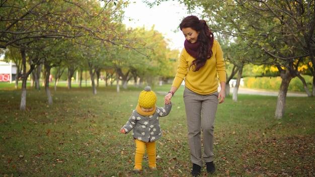 Outono positivo. mãe e filha vestidas com lindas roupas da moda caminham pelo parque nas folhas amarelas caídas em um dia quente de sol