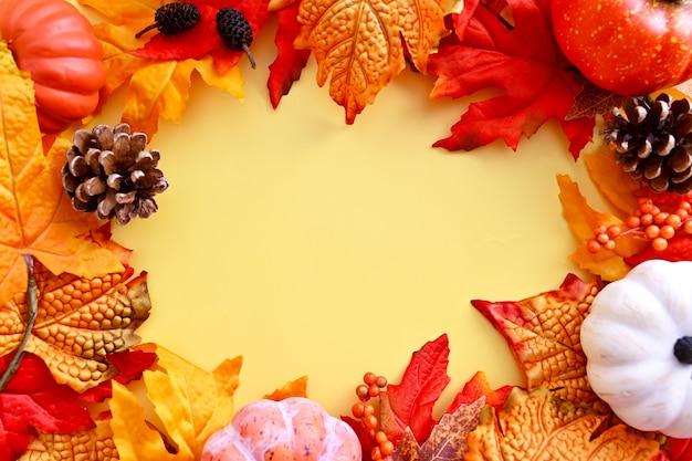 Outono, quadro de maquete de outono com folhas de laranja, pinhas e abóboras no fundo brilhante, copie o espaço para o texto