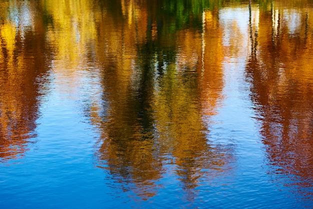 Outono. reflexo de árvores de outono coloridas borradas no rio