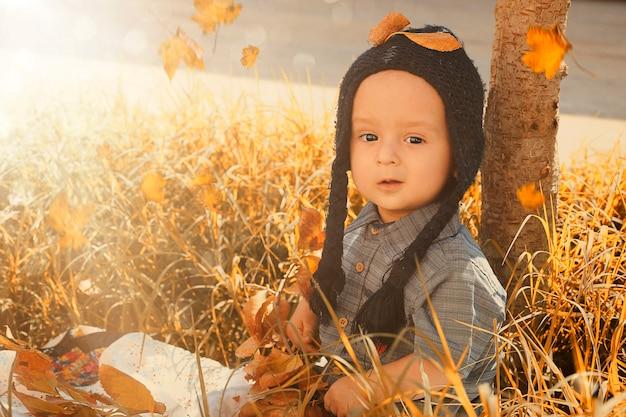 Outono retrato de criança de 2-3 anos de idade no jardim. outono. vista do close-up de alegre doce mestiça bebê menino de boné de malha