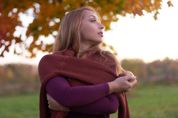 Outono retrato de menina bonita, envolvida numa camisola quente com maçã na mão
