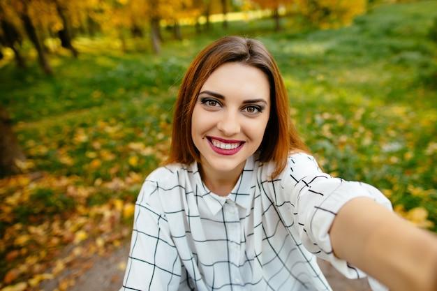Outono selfie retrato de uma garota excitada de gourgeus.