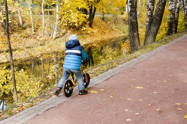 Outono. um menino anda de bicicleta ao longo de um caminho no parque perto do rio. ele cavalga na beira do penhasco.