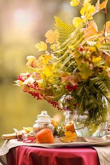 Outono. uma mesa posta nas margens do lago decorada com um buquê de folhas de outono. festa do chá. chás de frutas com limão, maçãs.