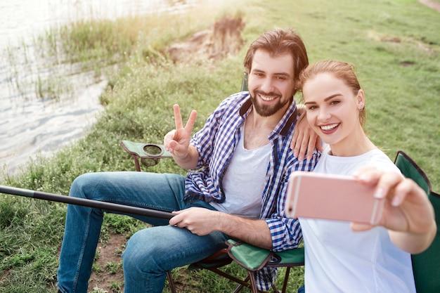 Outra foto da garota tirando selfie de si mesma e do marido. ela está fazendo isso com a câmera frontal no telefone. cara está sorrindo e mostrando o símbolo da peça. também ele está segurando o fim da vara de peixe.