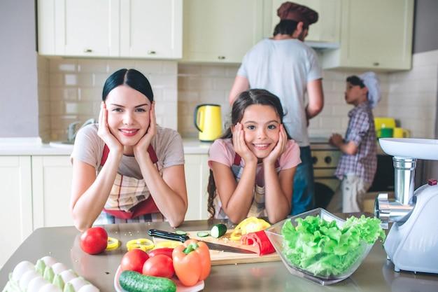 Outra foto de meninas inclinadas para a mesa com as mãos teóricas. eles olham e posam. garotos estão trabalhando atrás deles. thy cozinhar café da manhã.