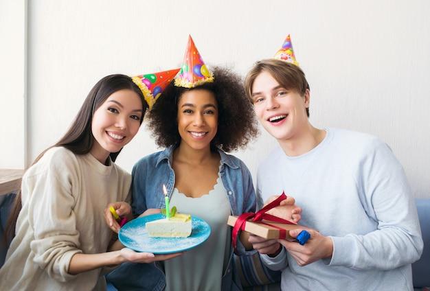 Outra foto de uma aniversariante e suas amigas. menina asiática tem um pedaço de bolo. o cara tem um presente nas mãos. todos eles são felizes.