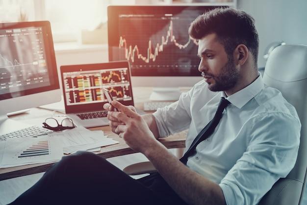 Outra mensagem de negócios. jovem empresário pensativo em trajes formais usando seu telefone inteligente enquanto está sentado no escritório