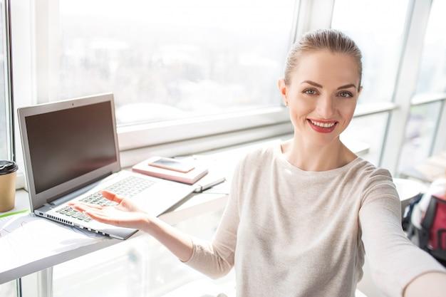 Outra selfie de trabalhador de escritório. ela está mostrando seu local de trabalho no escritório. está perto da janela. ela está muito orgulhosa disso.