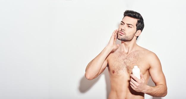 Outro belo tratamento de beleza homem aplica o hidratante em pé isolado sobre o branco