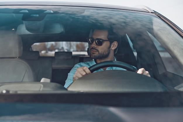 Outro dia agitado. jovem bonito olhando para longe enquanto dirige um carro de status