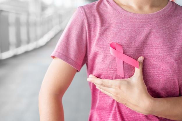 Outubro, mês da conscientização do câncer da mama, mulher de camiseta rosa com fita rosa para apoiar as pessoas que vivem e as doenças. cuidados de saúde, dia internacional da mulher e conceito do dia mundial do câncer