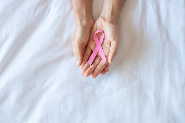 Outubro, mês de conscientização do câncer de mama, adulto mão de mulher segurando a fita rosa sobre fundo rosa para apoiar as pessoas que vivem e doenças. conceito do dia internacional da mulher, mãe e dia mundial do câncer