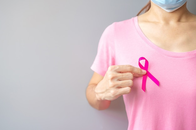 Outubro mês de conscientização sobre o câncer de mama, idosos mulher de camiseta rosa com a mão segurando a fita rosa para apoiar as pessoas que vivem e estão doentes. conceito do dia internacional da mulher, mãe e dia mundial do câncer