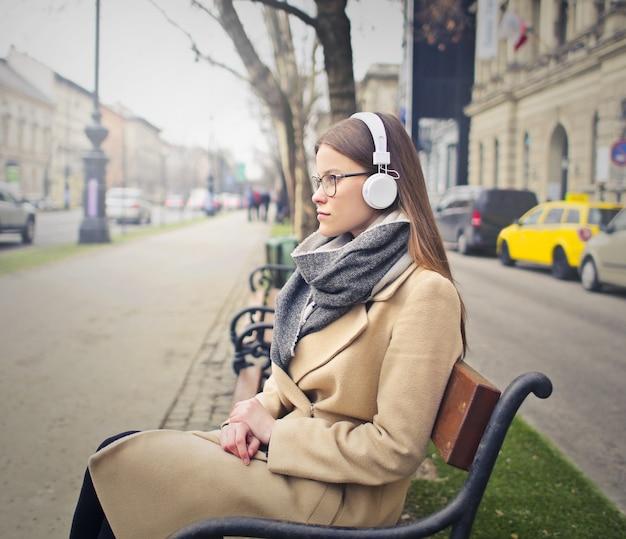 Ouvindo música em um banco da cidade
