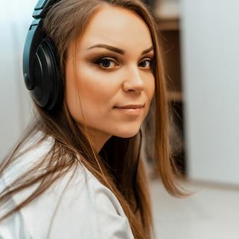 Ouvindo música. jovem menina bonita com grandes fones de ouvido na cabeça dela. fechar-se. lazer e música.