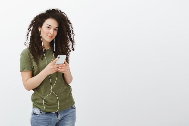 Ouvindo nova faixa do cantor favorito. retrato de uma mulher bonita, despreocupada e satisfeita com cabelo encaracolado