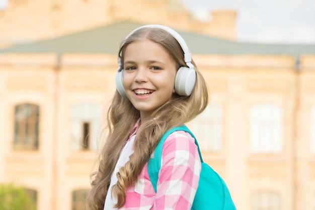 Ouvir e sonhar com facilidade. garota feliz gosta de ouvir música. a criança pequena pratica habilidades de escuta. curso de escuta. ensino à distância. treinamento remoto. escola e educação. vida moderna.