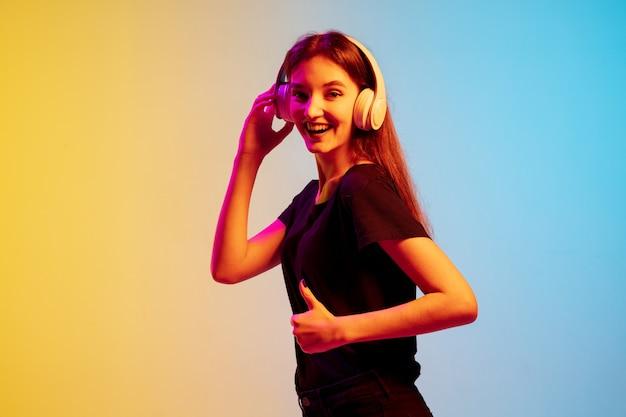 Ouvir música com fones de ouvido. retrato de jovem mulher caucasiana em fundo gradiente estúdio azul-amarelo em luz de néon. conceito de juventude, emoções humanas, expressão facial, vendas, anúncio.