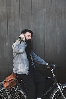 Ouvir música de ciclista em fones de ouvido em pé contra a parede de madeira preta