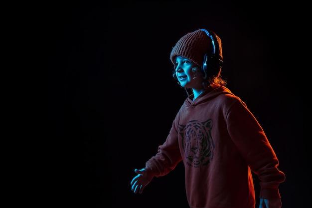 Ouvir música e dançar. retrato do menino caucasiano em fundo escuro do estúdio em luz de néon. lindo modelo cacheado. conceito de emoções humanas, expressão facial, vendas, anúncio, tecnologia moderna, gadgets.