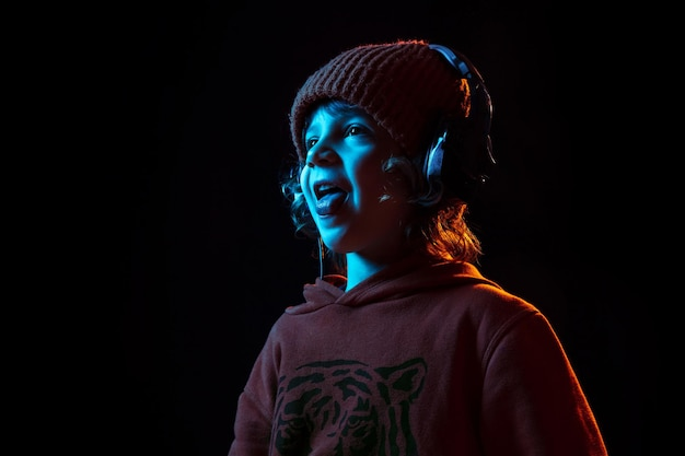 Ouvir música e dançar. retrato do menino caucasiano em fundo escuro do estúdio em luz de néon. lindo modelo cacheado.