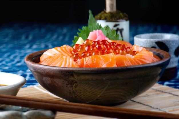 Ovas salmon do sashimi e dos salmões com arroz.
