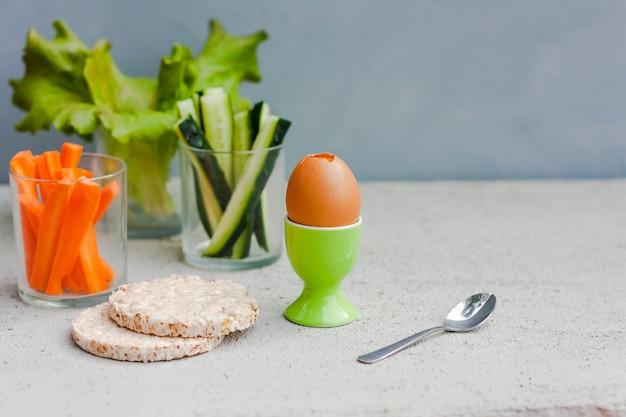 Ovo, alface, pepino e cenoura servidos em copo de vidro como lanche. café da manhã saudável.
