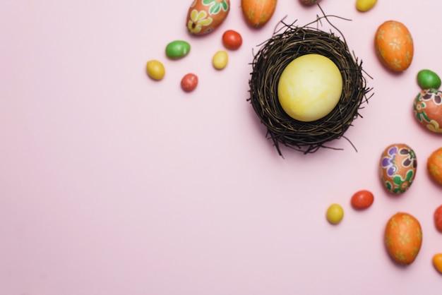 Ovo amarelo pintado para o feriado da páscoa em um ninho de galhos ao lado de doces e biscoitos de gengibre. cartão de páscoa em um fundo rosa