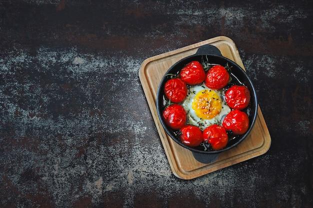 Ovo assado com tomate cereja e tomilho em uma frigideira de ferro fundido.