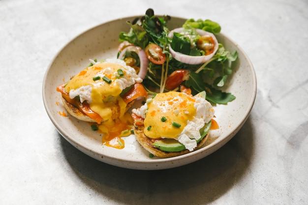 Ovo benedict com salmões e abacate, servido com salada na placa branca.