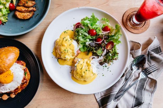 Ovo benedict servido com salada em chapa branca na mesa de madeira para delicioso café da manhã e