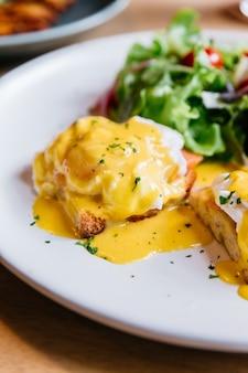 Ovo benedict servido com salada em chapa branca na mesa de madeira para delicioso café da manhã