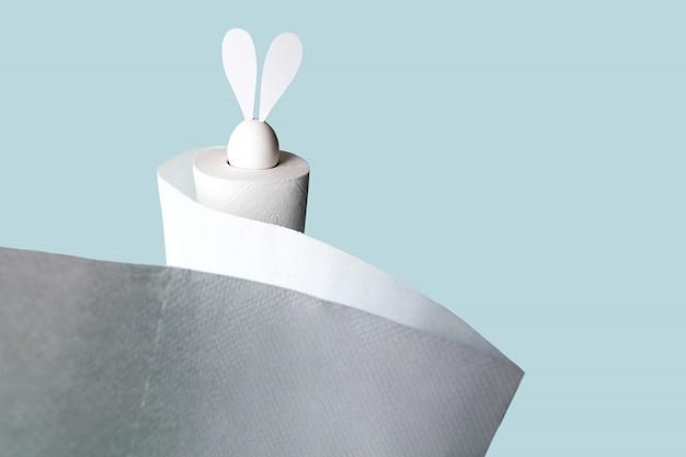 Ovo branco com orelhas de lebre em um rolo de papel higiênico. sombra dura sobre um fundo claro.