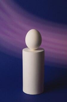 Ovo branco no pódio em neon e luz roxa