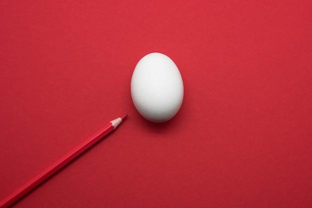 Ovo branco sobre fundo vermelho com caneta vermelha