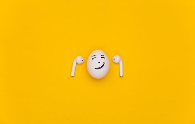 Ovo cara feliz ouve música com fones de ouvido sem fio em um fundo azul.