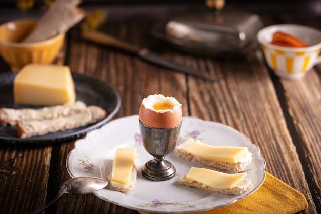 Ovo cozido em uma taça de prata com pão e queijo em uma mesa de madeira