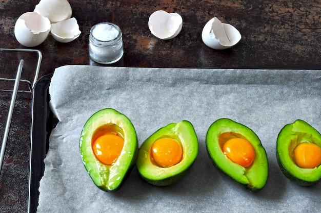 Ovo cru em abacate em uma assadeira. cozinhar abacate com ovo. keto receita de almoço.