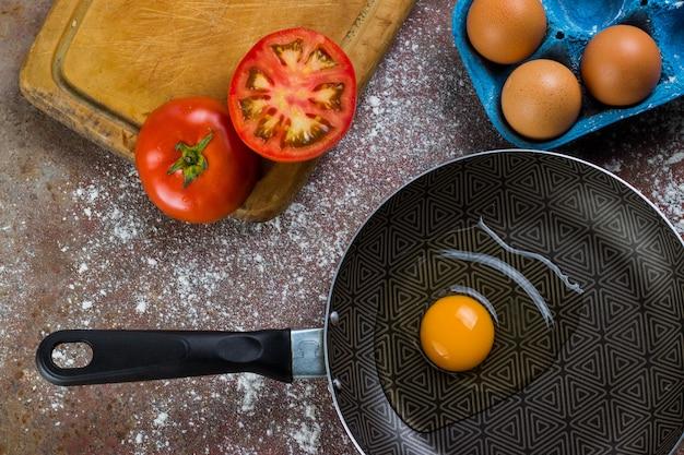 Ovo cru na panela ou panela acompanhado de tomate e ovos frescos na tábua e farinha