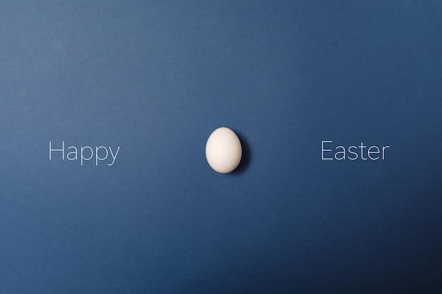 Ovo da páscoa branco com palavra feliz de easter, conceito do feriado. fundo azul