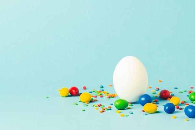 Ovo da páscoa branco e multi doces coloridos em uma superfície azul. conceito de celebração da páscoa.