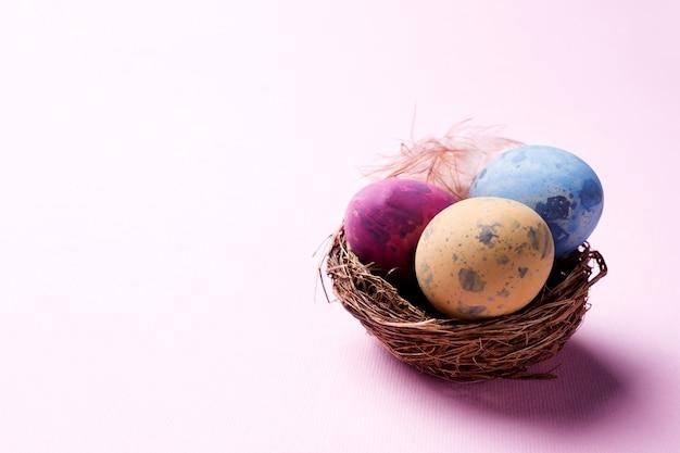 Ovo da páscoa colorido no ninho no fundo cor-de-rosa com espaço da cópia.