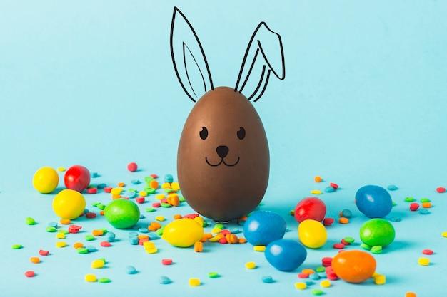 Ovo da páscoa do chocolate e multi doces coloridos em uma superfície azul. conceito de celebração da páscoa.