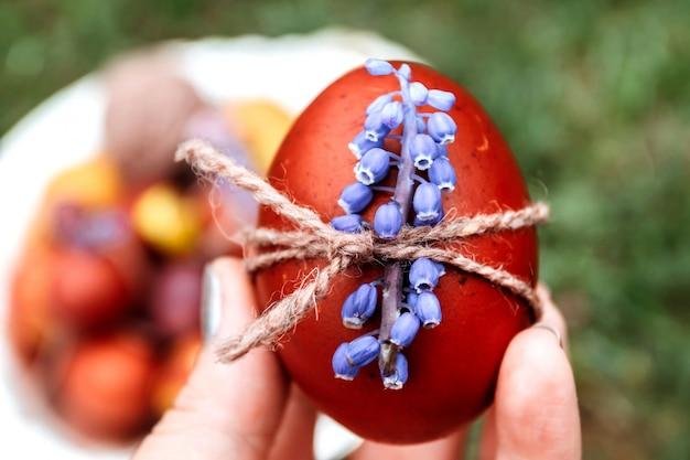 Ovo da páscoa vermelho decorado com a flor azul nas mãos das mulheres no fundo natural brilhante da grama.