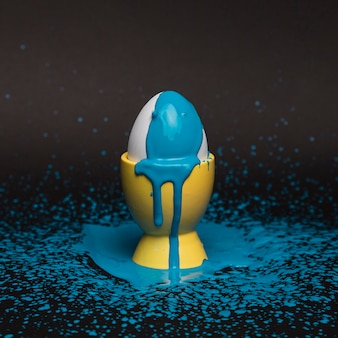 Ovo de alto ângulo no suporte com tinta azul